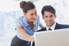 Gelukkige bedrijfsmensen die samen laptop bekijken Stock Afbeeldingen