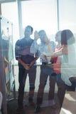 Gelukkige bedrijfsondernemers die zich door die whiteboard bevinden door glas wordt gezien stock foto's