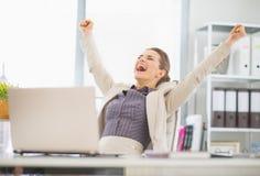 Gelukkige bedrijfsvrouw in bureau verheugend succes Royalty-vrije Stock Foto