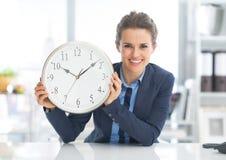 Gelukkige bedrijfsvrouw die klok tonen Stock Afbeelding