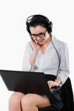 Gelukkige bedrijfsvrouw die met hoofdtelefoons voor een lapto zitten Royalty-vrije Stock Afbeelding
