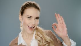 Gelukkige bedrijfsvrouw die o.k. in studio tonen De onderneemster toont okeyteken stock videobeelden