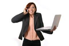 Gelukkige bedrijfsvrouw met rood haar die op mobiele de holdingslaptop van de celtelefoon spreken Stock Foto's
