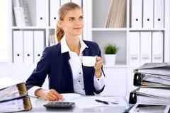 Gelukkige bedrijfsvrouw of vrouwelijke accountant die sommige notulen voor koffie en genoegen hebben op werkende plaats Royalty-vrije Stock Foto