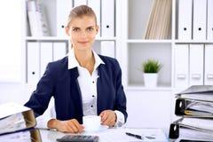 Gelukkige bedrijfsvrouw of vrouwelijke accountant die sommige notulen voor koffie en genoegen hebben op werkende plaats Stock Afbeeldingen