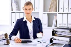 Gelukkige bedrijfsvrouw of vrouwelijke accountant die sommige notulen voor koffie en genoegen hebben op werkende plaats Royalty-vrije Stock Fotografie