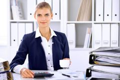 Gelukkige bedrijfsvrouw of vrouwelijke accountant die sommige notulen voor koffie en genoegen hebben op werkende plaats Stock Foto