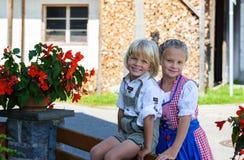 Gelukkige Beierse jongen met zuster op het landbouwbedrijf in Duitsland Stock Fotografie