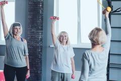 Gelukkige bejaarde dames die handen met domoren uitrekken bij gymnastiek royalty-vrije stock fotografie