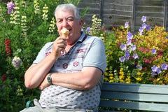 Gelukkige bejaarde die een ijsriem eet Royalty-vrije Stock Afbeeldingen
