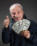 Gelukkige bejaarde die ventilator van geld toont Stock Fotografie