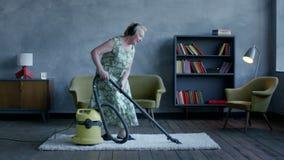 Gelukkige bejaarde het luisteren muziek op hoofdtelefoons en het dansen met een stofzuiger, huispret stock footage