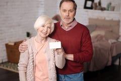 Gelukkige bejaarden die fmily kaart houden stock foto