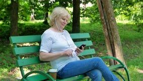 Gelukkige bejaardezitting op de bank in het park, gebruikend smartphone met oortelefoons en drinkend koffie Hoger Wijfje stock video