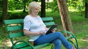 Gelukkige bejaardezitting op de bank in het park, gebruikend tablet met oortelefoons en drinkend koffie Hoger Wijfje stock videobeelden