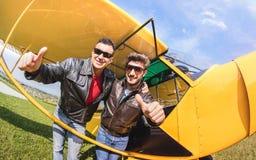 Gelukkige beste vrienden die selfie bij aeroclub met ultra licht vliegtuig nemen stock foto's