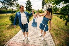 Gelukkige blije jonge familievader, moeder en weinig dochter die pret hebben die in openlucht, samen in de zomerpark spelen royalty-vrije stock afbeelding