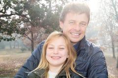 Gelukkige blije jonge vader met zijn leuke dochter die samen in de herfstpark die doorbrengend tijd genieten spelen van royalty-vrije stock fotografie