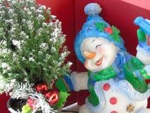 Gelukkige blije Kerstmissneeuwman die rond een Kerstmisboom schaatsen stock foto