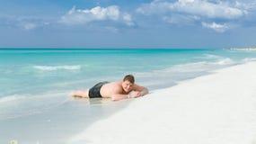 Gelukkige, blije tiener die op wit zand Cubaans strand liggen en van zijn vakantietijd genieten Royalty-vrije Stock Foto's