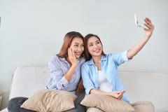 Gelukkige blije vrouwelijke vrienden die, genietend van besprekingen, die pret hebben thuis rusten royalty-vrije stock foto's