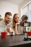 Gelukkige bloggers Paar die van positieve bloggers nieuwe video voor hun blog registreren, gebaarde mens die duimen tonen en royalty-vrije stock foto