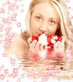 Gelukkige blond in water met rode en witte bloemen royalty-vrije stock foto's