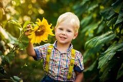 Gelukkige blonde jongen in een overhemd op zonnebloemgebied in openlucht Levensstijl, de zomertijd, echte emoties royalty-vrije stock fotografie