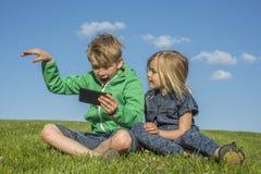 Gelukkige blonde kinderen die smartphone (het letten op film of speelspel) gebruiken zitting op het gras Royalty-vrije Stock Foto