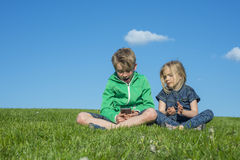 Gelukkige blonde kinderen die smartphone (het letten op film of speelspel) gebruiken zitting op het gras Royalty-vrije Stock Fotografie
