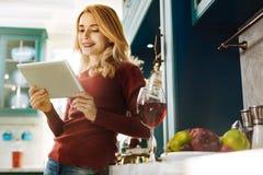 Gelukkige blonde vrouw die haar tablet gebruiken stock foto