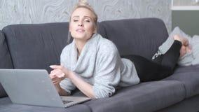 Gelukkige blonde vrouw die naar voren gebogen op bank en aan laptop computer werken liggen stock footage