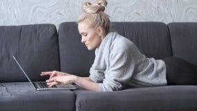 Gelukkige blonde vrouw die naar voren gebogen op bank en aan laptop computer werken liggen stock videobeelden