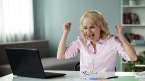 Gelukkige blonde vrouw die professionele voltooiing vieren, die dichtbij laptop zitten stock afbeeldingen
