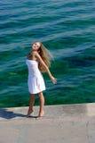 Gelukkige blonde in wit dichtbij overzees op pijler Stock Afbeeldingen