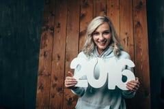 Gelukkige blondevrouw die 2016 aantallen houden Stock Afbeelding