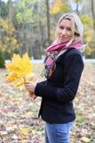 Gelukkige blondevrouw in zwart jasje in de herfstbos. stock foto's