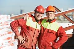 Gelukkige bouwersarbeiders bij bouwwerf Royalty-vrije Stock Foto's