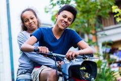 Gelukkige broer en zuster berijdende motorfiets stock afbeelding