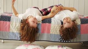 Gelukkige broer en zuster die en op het bed spelen lachen die zijn hoofd neer hangen stock footage