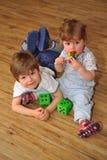 Gelukkige broer en zuster op houten vloer met speelgoed stock foto