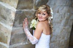 Gelukkige bruid dichtbij steenmuur Stock Afbeeldingen