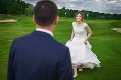 Gelukkige bruid die haar bruidegom op een weide lopen te ontmoeten Stock Afbeeldingen