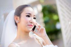 Gelukkige bruid die op celtelefoon spreken in huwelijkskleding Stock Foto