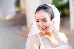 Gelukkige bruid die op celtelefoon spreken in huwelijkskleding Royalty-vrije Stock Foto
