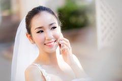 Gelukkige bruid die op celtelefoon spreken in huwelijkskleding Royalty-vrije Stock Foto's