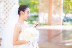 Gelukkige bruid die op celtelefoon spreken in huwelijkskleding Royalty-vrije Stock Afbeelding