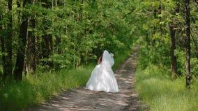 Gelukkige bruid die op de weg in het hout springen stock videobeelden