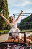 Gelukkige bruid die van klassieke convertibel gillen Stock Afbeeldingen
