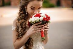 Gelukkige bruid in een huwelijkskleding met een vlechtkapsel die een boeket van rozen snuiven stock foto's